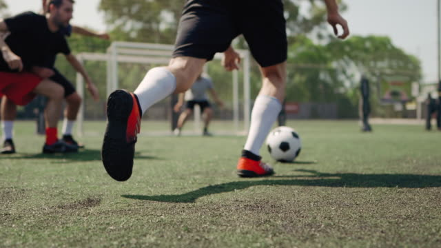vidéos et rushes de vue d'angle bas du joueur masculin de football donnant le coup de pied bille de football - football