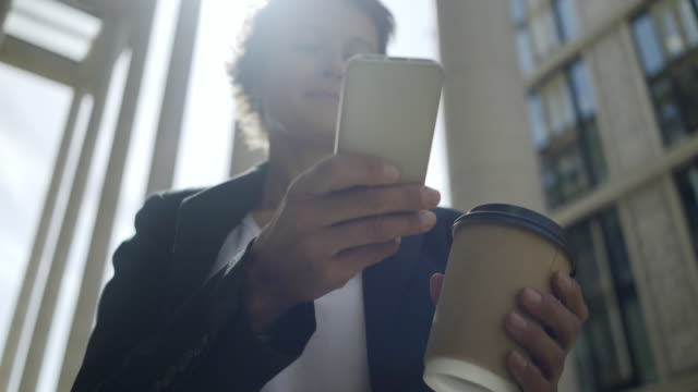 Low angle view of middle aged businesswoman text messaging on her smartphone outdoors, takeaway paper coffee cup in her hand Low angle view of middle aged businesswoman text messaging on her smartphone outdoors, takeaway paper coffee cup in her hand short hair stock videos & royalty-free footage