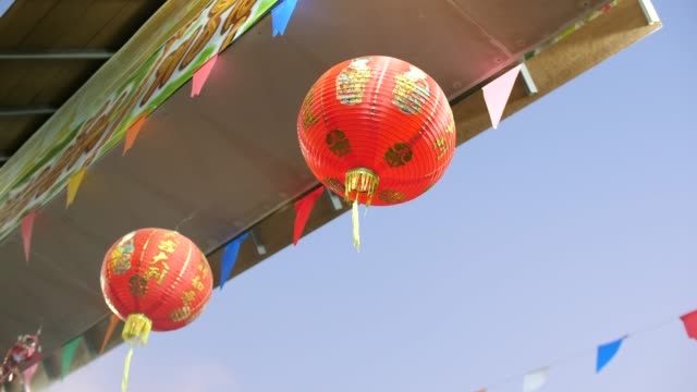 low angle view of red chinese lanterns under temple gate - китайский фонарь стоковые видео и кадры b-roll