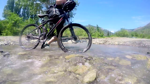 Low angle view of traveler woman pushing bicycle crossing mountain stream video