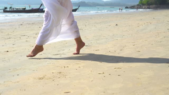 låg vinkel syn på ung kvinna som springer mot havet med glatt humör - på tå bildbanksvideor och videomaterial från bakom kulisserna