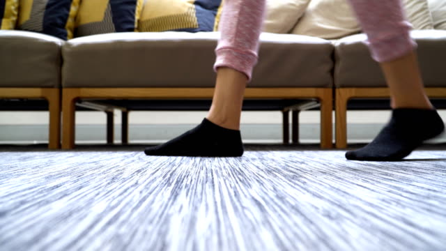 low angle view on the floor: woman's feet with sock walking in domestic room low angle view on the floor: woman's feet with sock walking in domestic room sock stock videos & royalty-free footage