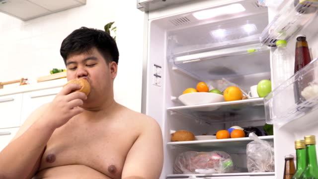 低視野角: 太りすぎの冷蔵庫からタイ人が食べるパン - 体への関心点の映像素材/bロール