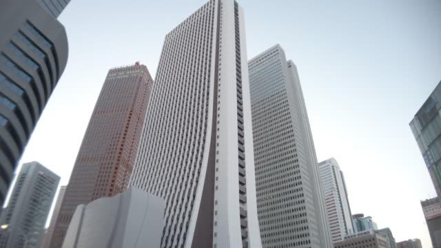 4k 로우 앵글 뷰, 패닝, 틸트 업, 오피스 빌딩 및 신주쿠의 하늘 - 패닝 스톡 비디오 및 b-롤 화면