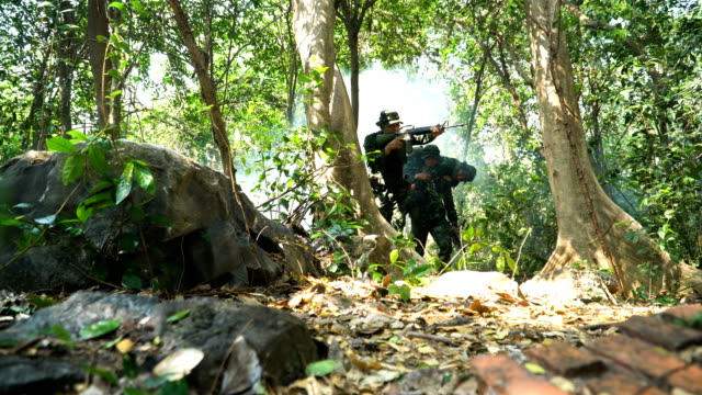 widok niski kąt: żołnierz niosący rannych z lasu tropikalnego - rana filmów i materiałów b-roll