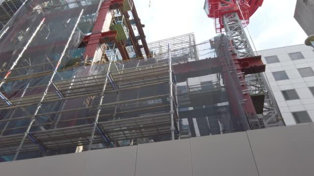 vídeos y material grabado en eventos de stock de 4k vista de ángulo bajo inclinación hacia arriba . grúas de construcción y construcción en tokio, japón. - material de construcción