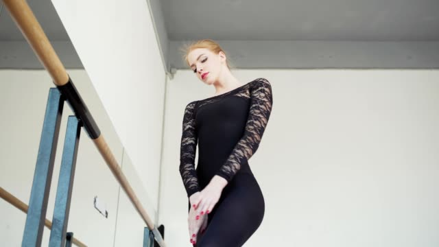 low angle view tracking shot of beautiful and elegant young ballerina in black lace leotard practicing at barre in dance studio - body abbigliamento sportivo video stock e b–roll