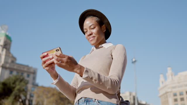 Low angle view video of influencer texting on mobile phone outdoors