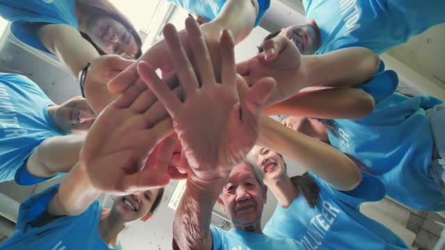 stockvideo's en b-roll-footage met low angle view, happy aziatische groep mensen zetten hun handen samen van de gemeenschap vrijwilligers en handen in een huddle voor de gemeenschap project. vriendschap, teamwork, succes, vrijwilliger, liefdadigheid, leiderschap, mensen, ouderen, charity co - huddle