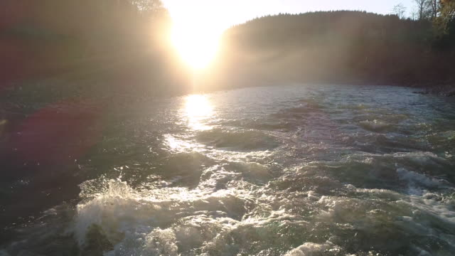 Low Drone Flight Over River Rapid Waves in Hazy Sunset video