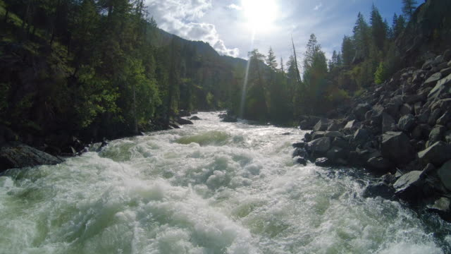 low drone flying backwards over raging river rapids - summer background filmów i materiałów b-roll