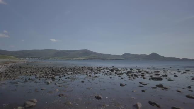 vídeos de stock e filmes b-roll de 88. low drone over water towards mountains kerry waterville beach, co kerry, ireland - linha do horizonte sobre terra