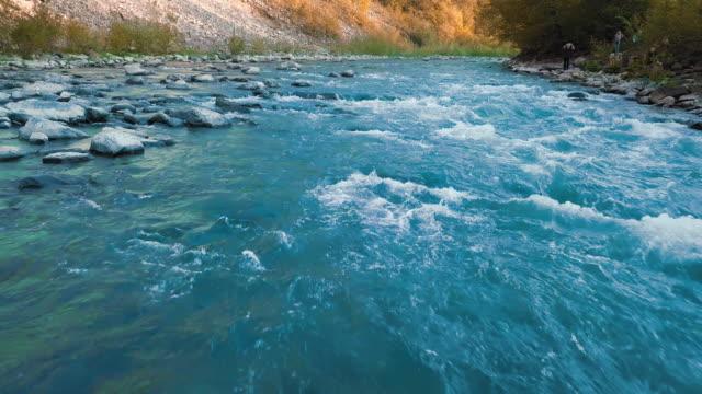 急いで山川、そして山の中で青緑色の結晶石上飛行を低します。背景には、観光客が撮影されています。日没の時間。太陽の光では、オレンジ色の炎を与えます。レジャー、旅行、エンター� - 野生動物旅行点の映像素材/bロール