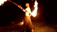 istock Low key. A young male with long hair and a naked torso rotates a burning torch outdoors on a black night video slow motion near the fires. Modern fakir does tricks with a burning staff 1205731247