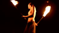 istock Low key. Young male with long hair and bare torso rotates burning torch outdoors on a black night video slow motion. Modern fakir does tricks with a burning staff 1205727614