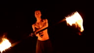 istock Low key. Young male with long hair and bare torso rotates burning torch outdoors on a black night video slow motion. Modern fakir does tricks with a burning staff 1205728798