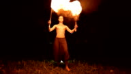 istock Low key. Young male with long hair and bare torso rotates burning torch outdoors on a black night video slow motion. Modern fakir does tricks with a burning staff 1205729595