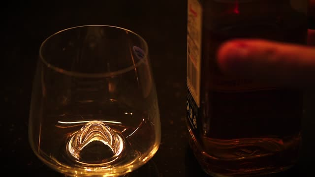 low light footage of bourbon, cognac or whiskey poured in wine glass on dark table. - decanter video stock e b–roll