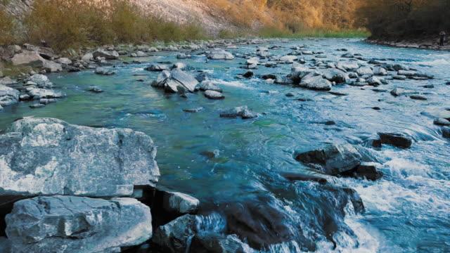 急いで山川と山の間で青緑色の結晶石低パノラマ飛行。日没の時間。太陽の光では、オレンジ色の炎を与えます。泌尿器科の病気、前立腺炎、腎臓結石、決定の自由治療の概念 - 野生動物旅行点の映像素材/bロール