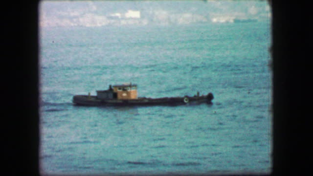 1944: Low profile tugboat traveling solo across the hazy harbor waters. video