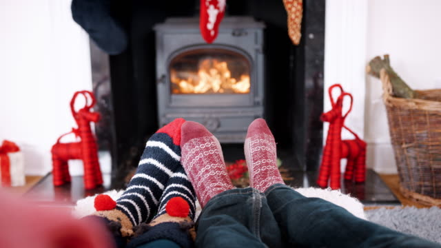 Low section of couple wearing Christmas socks relaxing in front of fireplace, detail Low section of couple wearing Christmas socks relaxing in front of fireplace, detail christmas stocking stock videos & royalty-free footage
