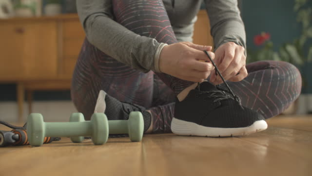 Low Section Of Fit Woman Tying Shoe Lace By Dumbbells video