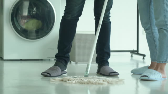 Low section of man cleaning the floor with mop