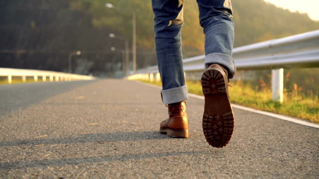 SLO MO Low section of man in boot walking in the morning video