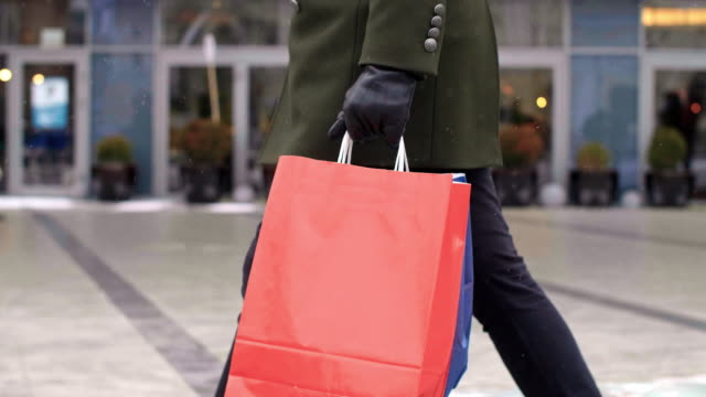 low section of man with shopping bags walking the street - borsa della spesa video stock e b–roll