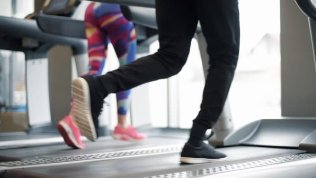 vídeos de stock e filmes b-roll de low section of running couple - aparelho de musculação