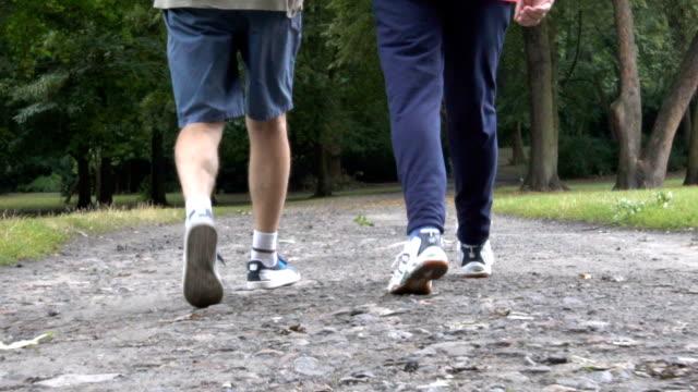 Low section of senior men walking on dirt road video