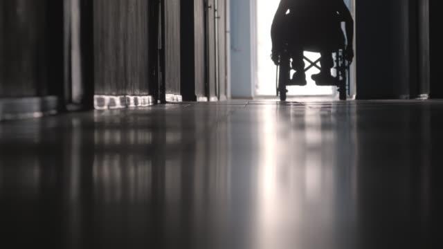 låga delen av silhuetten av handikappade patienten rider rullstol - hospital studio bildbanksvideor och videomaterial från bakom kulisserna
