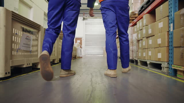 Low section of two male workers walking in the large distribution warehouse