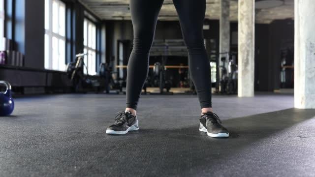 low section of woman lifting kettlebell in gym - giria filmów i materiałów b-roll