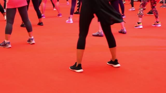 low-section-view-gruppe von frauen, die während des übungsunterrichts auf rotem boden tanzen - fitnesskurs stock-videos und b-roll-filmmaterial