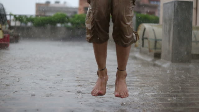 Low section view of a woman jumping in rain video