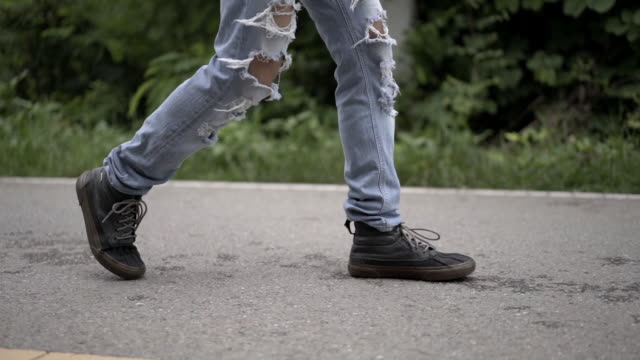 Low section view of Asian man in Fashion  Straight Slim Pants Damage Hole Denim Jean Pants Ripped Skinny Trousers Walking