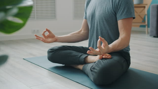Low shot of anonymous man meditating on yoga mat sitting in lotus position Low shot of anonymous man meditating on yoga mat sitting in lotus position with hands in namaste then in mudra gestures. People and relaxation concept. cross legged stock videos & royalty-free footage