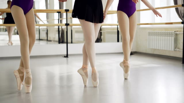 low shot of female legs in ballet shoes doing plie then dancing on tiptoes on floor of light studio. choreography, classical ballet, art and children concept. - classical architecture stock videos & royalty-free footage