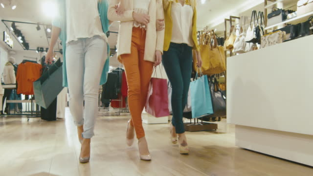 Low shot of female legs walking towards the camera through a department store in colorful garments with shopping bags. ビデオ