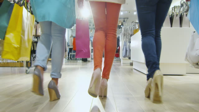 Low shot of three girls that are walking through a clothing store in colorful garments. video