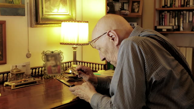 vidéos et rushes de homme ayant la vue faible utilise un téléphone mobile avec une loupe: vieux, senior, problèmes - vaisselle picto