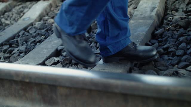 Low view of male engineer's legs walking on the railway video