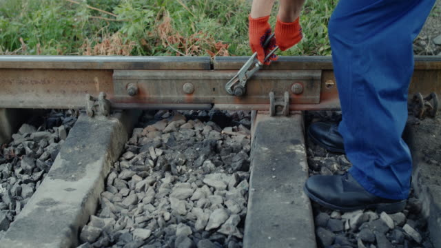 Low view of railroader unscrewing the nuts on the rail with repair key video