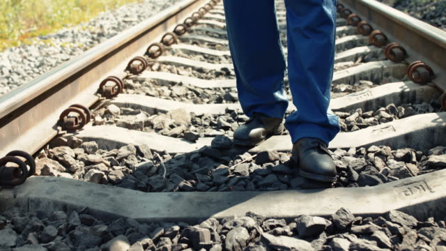 Low view of railroader with tablet walking on the railway video