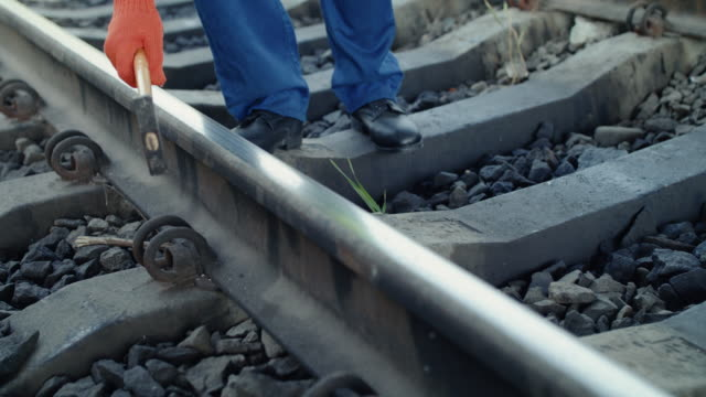 Low view of railroader's hand checks the rails serviceability with hammer video