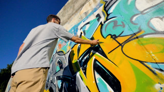 A low view on a man restoring a graffiti painting. video