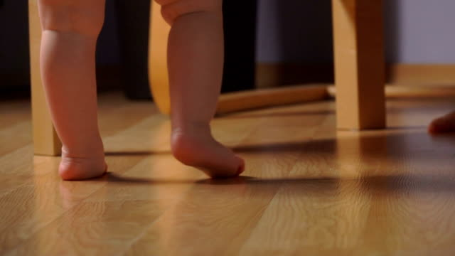 Low-angle view of little adorable baby standing on the tiptoes next to the chair - video