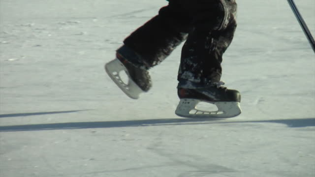 lower angle view of child playing hockey on pond - hockey stock videos and b-roll footage