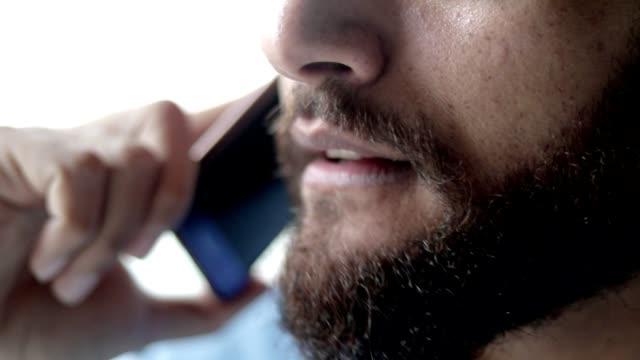 vídeos de stock, filmes e b-roll de rosto inferior de homem barbudo mestiço falando no celular - boca